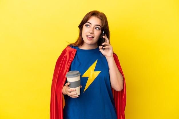 Super hero rothaarige frau isoliert auf gelbem hintergrund mit kaffee zum mitnehmen und einem handy