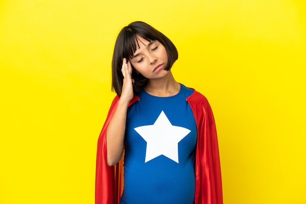 Super hero schwangere frau isoliert auf gelbem hintergrund mit kopfschmerzen