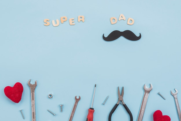 Super papa inschrift mit werkzeugen und papierschnurrbart