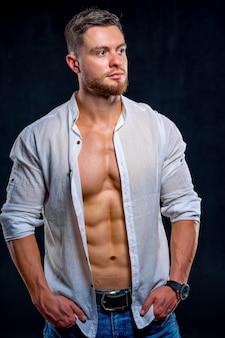 Super sexy mann mit braunen bauchmuskeln und brust. sportlicher mann mit aufgeknöpftem weißem hemd auf dunklem hintergrund. studioportrait