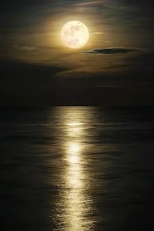 Super vollmond und wolke am gelben himmel über dem ozeanhorizont um mitternacht, mondlicht reflektieren die wasseroberfläche und welle, schöne naturlandschaftsansicht bei nachtszene des meeres für den hintergrund