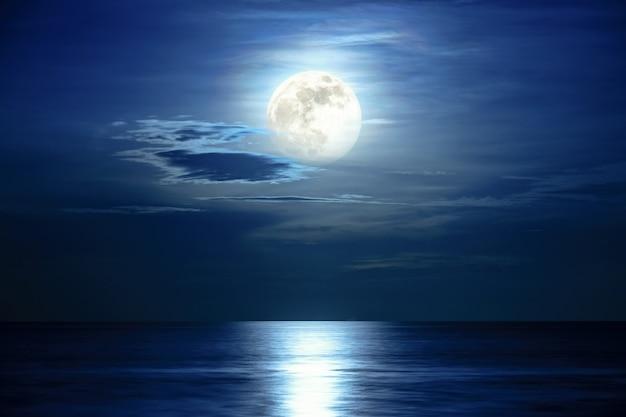 Super vollmond und wolken am blauen himmel über dem ozeanhorizont um mitternacht, mondlicht reflektieren die wasseroberfläche und welle, schöne naturlandschaftsansicht bei nachtszene des meeres für den hintergrund