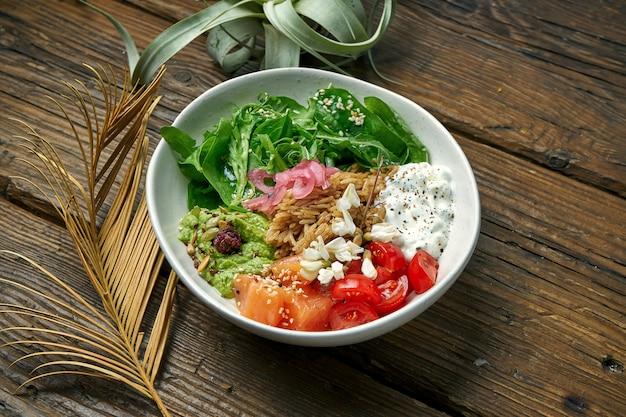 Superfood - eine schüssel mit reis, lachs, guacamole, pochiertem ei und kirschtomaten, gewürzt mit griechischem joghurt auf einem holztisch. ausgewogenes essen