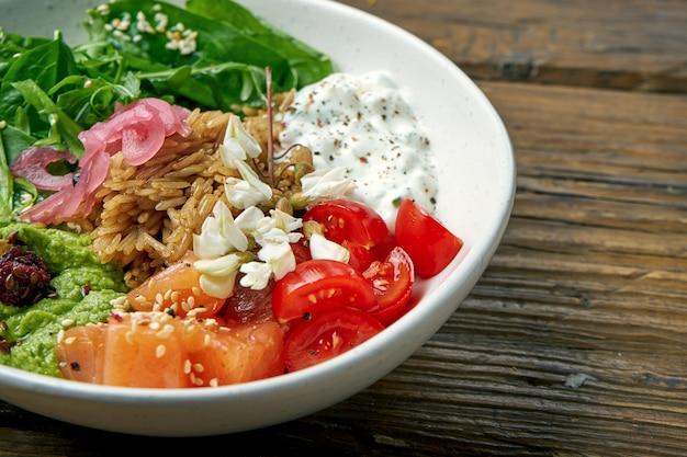 Superfood - eine schüssel mit reis, lachs, guacamole, pochiertem ei und kirschtomaten, gewürzt mit griechischem joghurt auf holz. ausgewogenes essen