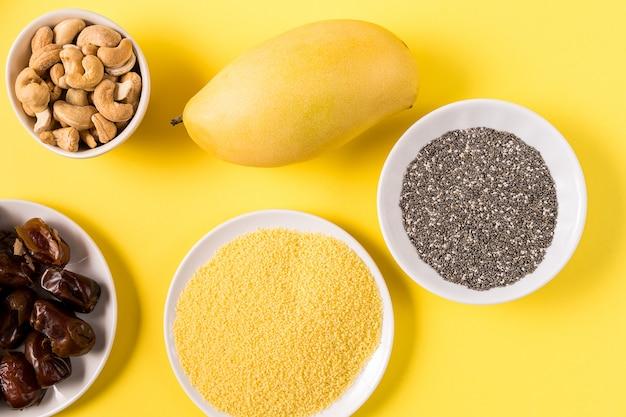 Superfoods in den schüsseln auf gelbem hintergrund.