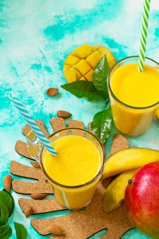 Superfoods und gesundheits- oder detox-diät-lebensmittelkonzept frucht-smoothies in glasflaschen mit mango