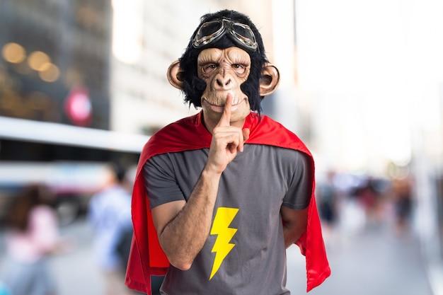Superheld affe mann macht stille geste auf unfocused hintergrund