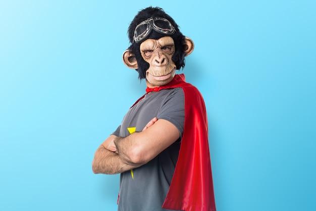 Superheld affe mann mit seinen armen auf buntem hintergrund gekreuzt