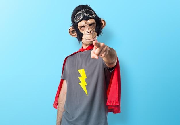 Superheld affe mann zeigt auf die front auf bunten hintergrund