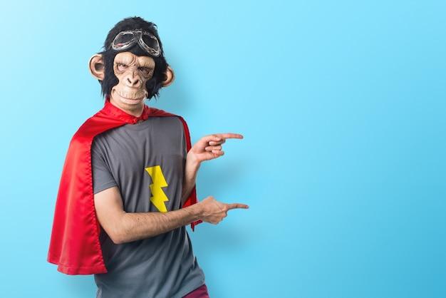Superheld affe mann zeigt auf die laterale auf bunten hintergrund