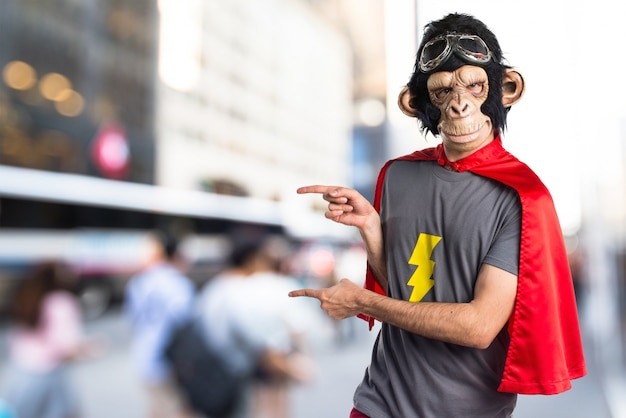 Superheld affe mann zeigt auf die laterale auf unfocused hintergrund