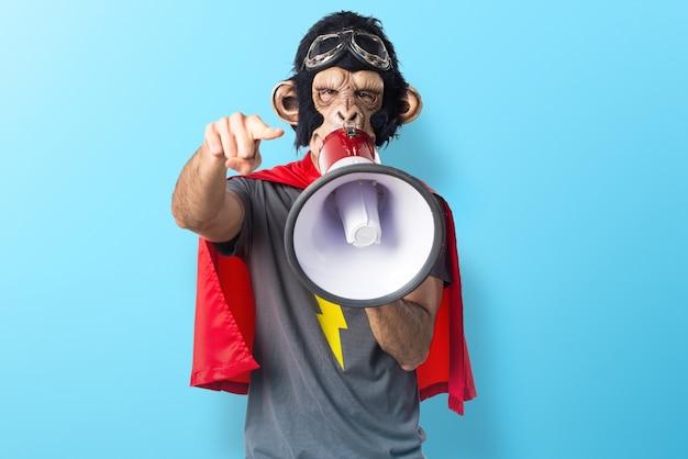 Superheld-affenmann, der durch megaphon auf buntem hintergrund schreit