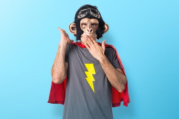 Superheld-affenmann, der überraschungsgeste auf buntem hintergrund tut