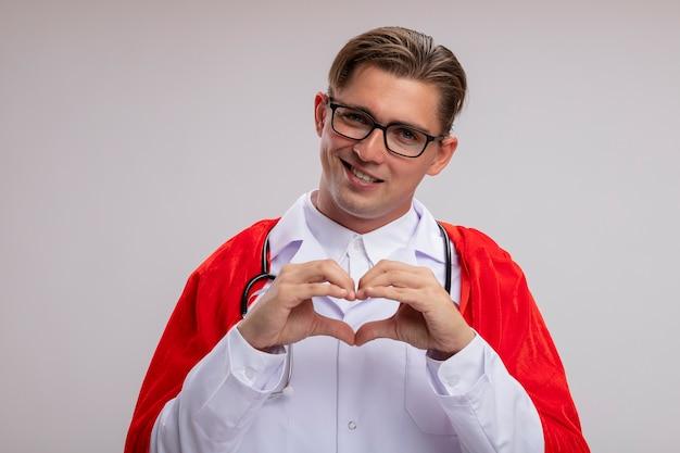 Superheld doktormann, der weißen mantel im roten umhang und in den gläsern mit stethoskop um hals trägt, macht herzgeste mit den fingern, die fröhlich über weißer wand stehend lächeln