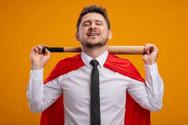 Superheld-geschäftsmann im roten umhang, der baseballschläger auf den schultern hält, die zuversichtlich über orange wand stehend lächeln