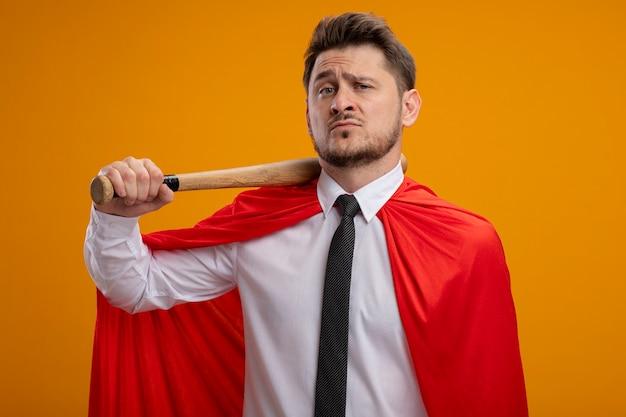 Superheld-geschäftsmann im roten umhang, der baseballschläger auf seiner schulter hält, die zuversichtlich steht, über orange wand zu stehen