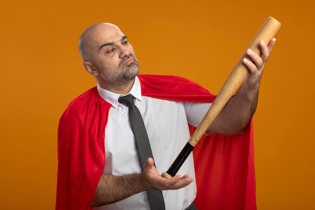 Superheld geschäftsmann im roten umhang, der baseballschläger hält, der es fasziniert betrachtet