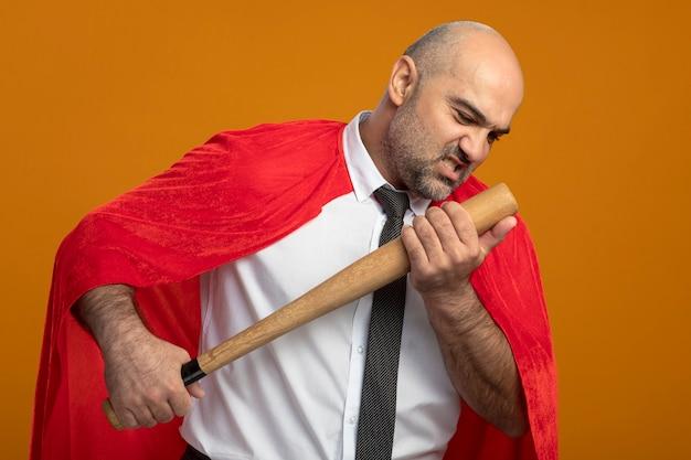 Superheld-geschäftsmann im roten umhang, der baseballschläger hält, der es mit dem wütenden gesicht betrachtet, das über orange wand steht