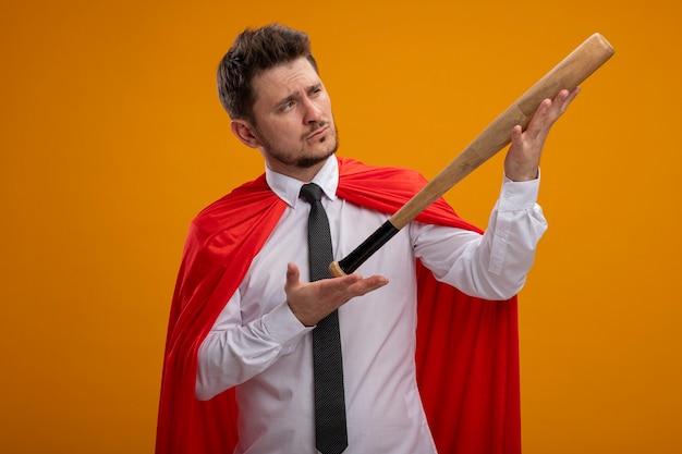 Superheld-geschäftsmann im roten umhang, der baseballschläger hält, der es mit ernstem gesicht betrachtet, das über orange hintergrund steht