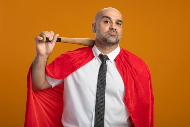 Superheld-geschäftsmann im roten umhang, der baseballschläger hält, der vorne mit ernstem sicherem ausdruck steht, der über orange wand steht
