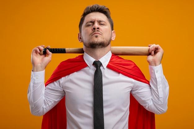 Superheld-geschäftsmann im roten umhang, der baseballschläger hinter seinem hals hält und zuversichtlich steht, über orange wand zu stehen