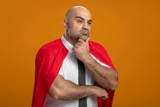 Superheld geschäftsmann im roten umhang, der mit nachdenklichem ausdruck auf gesichtsdenken beiseite schaut
