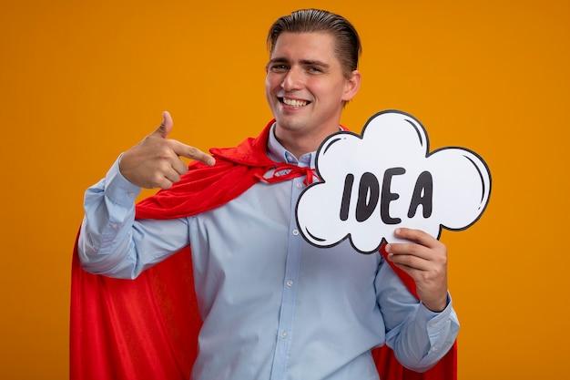 Superheld-geschäftsmann im roten umhang, der sprachblasenzeichen mit wortidee hält, die mit zeigefinger darauf lächelnd über orange hintergrund steht