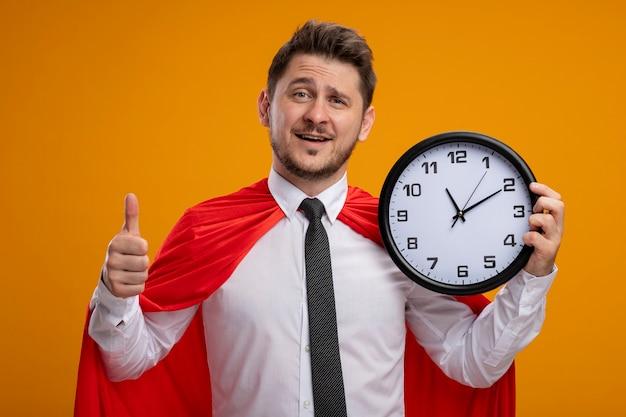 Superheld-geschäftsmann im roten umhang, der wanduhr hält, die kamera betrachtet, die fröhlich daumen zeigt, die oben über orange hintergrund stehen