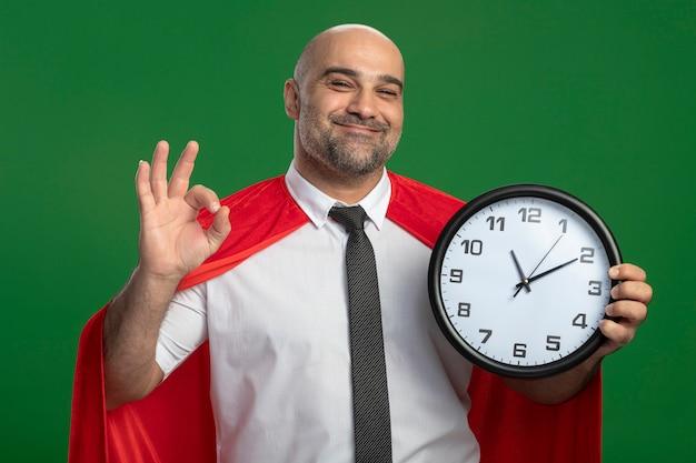 Superheld-geschäftsmann im roten umhang, der wanduhr hält, die vorne lächelnd fröhlich zeigt ok zeichen steht über grüner wand