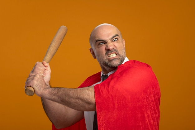 Superheld geschäftsmann im roten umhang schwingenden baseballschläger mit wütendem aggressivem ausdruck, der wild geht