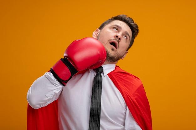Superheld geschäftsmann im roten umhang und in boxhandschuhen, die sich stehend über orange wand schlagen