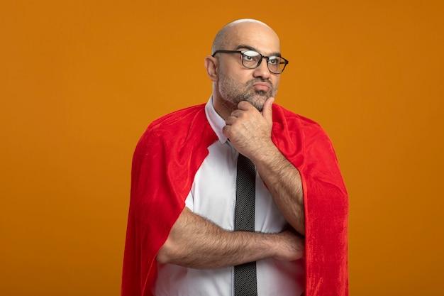 Superheld-geschäftsmann im roten umhang und in den gläsern, die beiseite mit hand auf kinn denken, das über orange wand steht