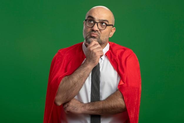 Superheld-geschäftsmann im roten umhang und in den gläsern, die beiseite mit nachdenklichem ausdruck auf dem gesicht denken, das über grüner wand steht