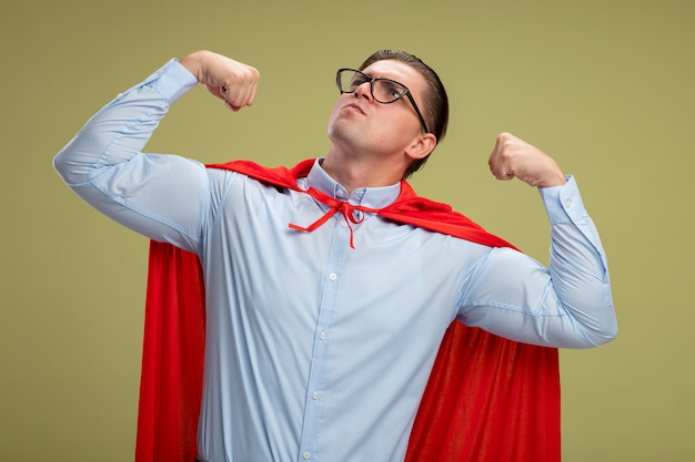 Superheld-geschäftsmann im roten umhang und in den gläsern, die fäuste erheben, die an der kamera aufstellen, die stärke und mut zeigt, die über hellem hintergrund stehen