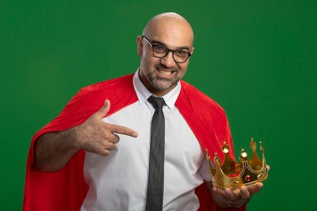 Superheld-geschäftsmann im roten umhang und in den gläsern, die krone halten, die selbstbewusstes lächelndes pointign mit zeigefinger an der krone lächelnd stehen über grüner wand stehen