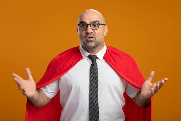 Superheld-geschäftsmann im roten umhang und in den gläsern, die verwirrt mit erhobenen armen stehen, die über orange wand stehen