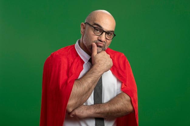 Superheld-geschäftsmann im roten umhang und in den gläsern, die vorne mit hand auf kinn denken, das über grüner wand steht