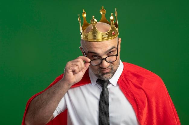 Superheld-geschäftsmann im roten umhang und in der brille, die krone trägt, die kamera genau betrachtet, die seine brille berührt, die über grüner wand steht