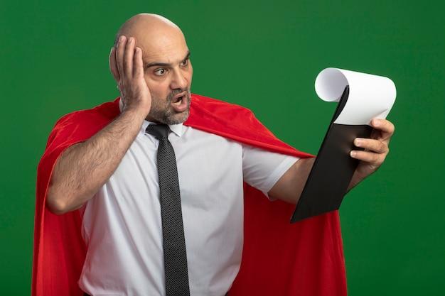 Superheld geschäftsmann im roten umhang zeigt zwischenablage mit leeren seiten, die sie verwirrt und überrascht betrachten, die über grüner wand stehen