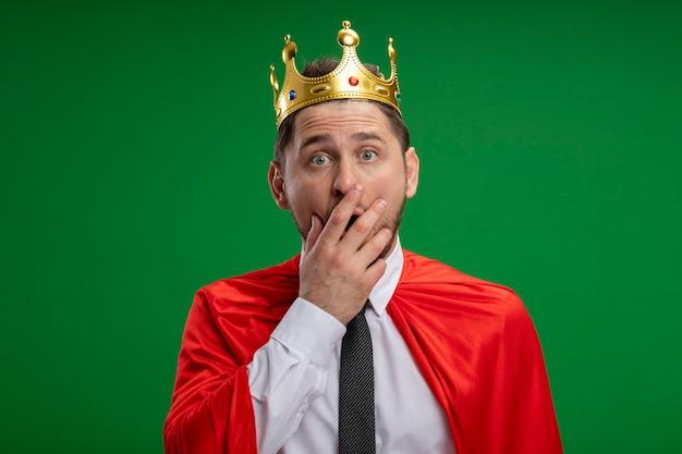 Superheld-geschäftsmann in der roten umhang tragenden krone, die kamera betrachtet, die schockiert ist, den mund mit der hand stehend über grünem hintergrund bedeckt