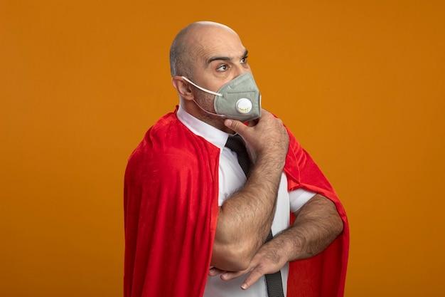 Superheld geschäftsmann in der schützenden gesichtsmaske und im roten umhang, die mit nachdenklichem ausdruck auf gesicht mit hand auf kinn denkend beiseite schauen