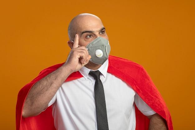 Superheld geschäftsmann in der schützenden gesichtsmaske und im roten umhang, die mit nachdenklichem ausdruck auf gesichtsdenken beiseite schauen