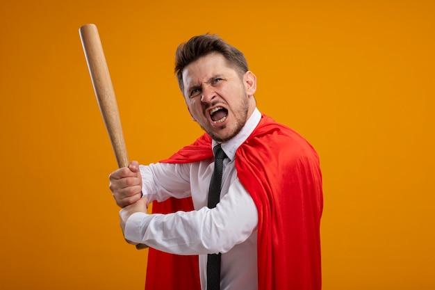 Superheld geschäftsmann in rotem umhang schwingenden baseballschläger, der mit aggressivem ausdruck über orange wand steht schreit