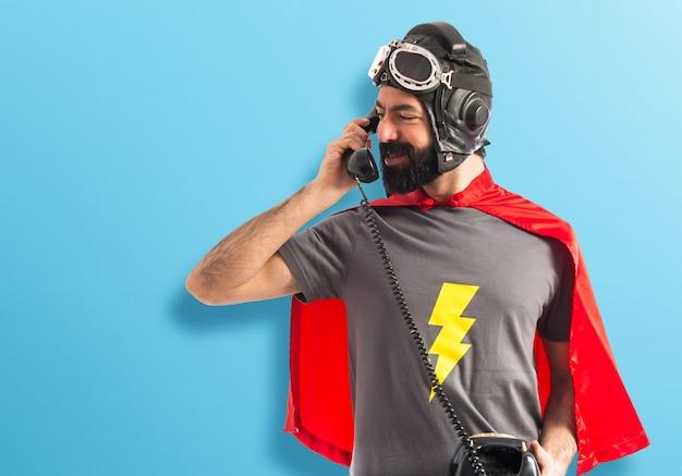 Superheld im gespräch mit vintage telefon auf buntem hintergrund