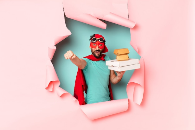 Superheld mit lieferessen hinter zerbrochener papierwand
