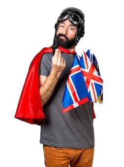 Superheld mit vielen fahnen, die geldgeste machen