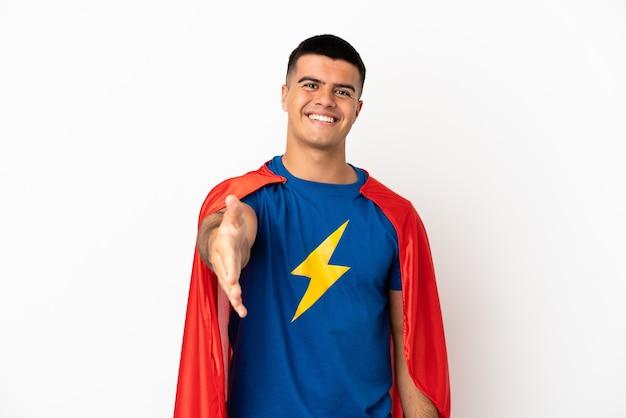 Superheld über isoliertem weißem hintergrund, der hände schüttelt, um ein gutes geschäft abzuschließen