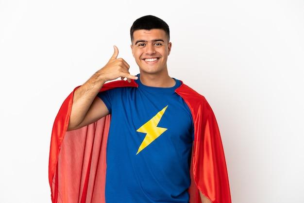 Superheld über isoliertem weißem hintergrund, der telefongeste macht. ruf mich zurück zeichen