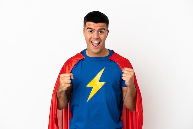 Superheld über isoliertem weißem hintergrund feiert einen sieg in siegerposition