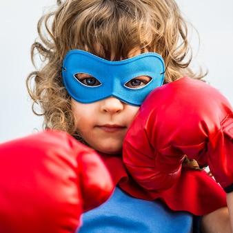 Superhelden-kind mit boxhandschuhen vor blauem himmelshintergrund. frauenpower und feminismus-konzept